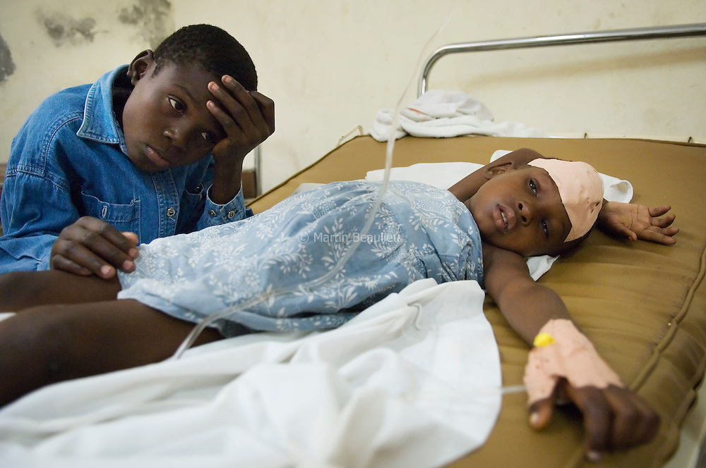 Hector, 14-years-old, looks after sister Ami, 7, who was accidentally shot on the street a few weeks ago. //// Hector, 14 ans, veille sur sa soeur Ami, 7 ans, accidentellement blessée par balle.