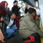 Godana Jatani, right, and Mulunesh Nora, collapsing at left, react to the sight of a dried pool of blood inside the Philadelphia Cheese Steak restaurant during a memorial to the murdered owner of the restaurant, Dejene Berecha on Feburary 2, 2008 in Seattle.  The Ethiopian immigrant was recently married and planned to relocate the restaurant soon.
