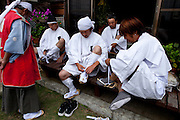 Men in traditional clothes wearing their straw sandals as they go out of the house of Samurai Fuku Taisho during the Soma Nomaoi festival