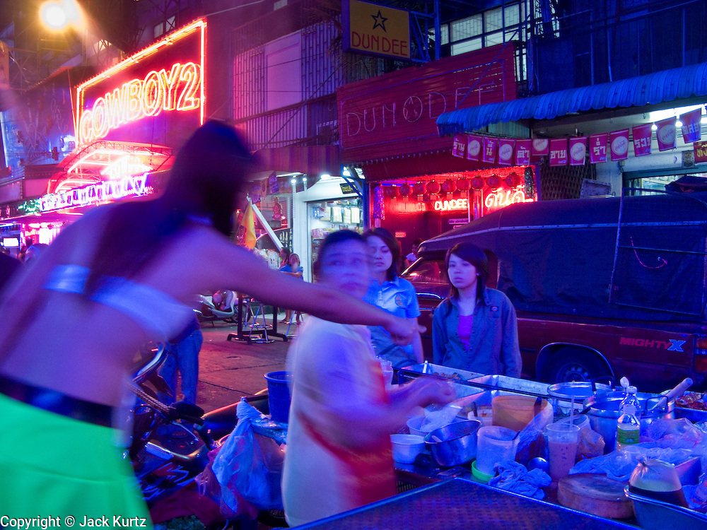 """29 FEBRUARY 2008 -- BANGKOK, THAILAND:  A push cart food vendor does business with workers on Soi """"Cowboy"""" one of the adult entertainment districts in Bangkok, Thailand.   Photo by Jack Kurtz/ZUMA Press"""