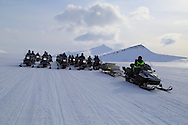 Tourists snowmobile in April between Longyearbyen and Barentsburg; Svalbard, Norway.
