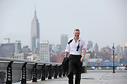 handsome middle aged man in a tuxedo shirt standing on a pier in Hoboken, NJ after a rain storm overlooking New York City.