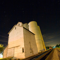The small grain elevator in the tiny town of Danforth, IL sits beside a railroad main line, even complete with it's own track for loading grain hoppers when shipments demand. A starry summer night sky looms overhead.