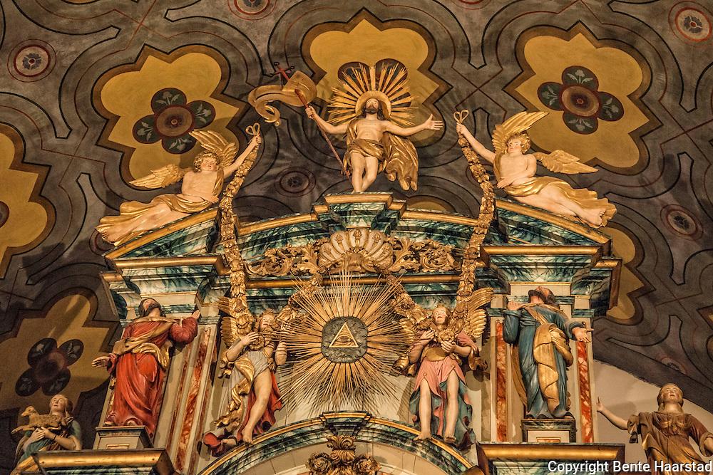 Altertavle, Vår Frue kirke i Trondheim. brosteinkorset i Vår Frue kirke, som er en åpen kirke, en omsorgskirke, drevet av Kirkens Bymisjon i Trondheim. Altertavlen er laget i 1742-44 for  Nidarosdomen, den har vært i Vår Frue kirke siden 1837. Den er et barokkverk i jesuitterstil, formet som en portal rundt tre tema. Nederst et lite maleri av nattverden, midt i et maleri av den korsfestede Kristus, og øverst en skulptur av den triumferende Kristus. Portalen er flankert av bibelpersoner og kardinaldyder. Nederst står Moses med lovtavlene og Aron med røkelseskar, flankert av Fides med alterkalk og Caritas (kjærligheten) med et barn på armen. Over portalen Pietas som bærer et lam, og Spes med et anker. Over portalen stråler Guds øye, flankert av to gammeltestamentlige profeter, som holder et blomstergirlander båret av to engler som hyller den oppstandne Kristus. Samlet høyde er ca. 10 meter, og den er trolig Norges største (Wikipedia).
