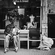 Man with child in his arms sitting out side a coffee shop in central Amsterdam while his wife is inside shopping