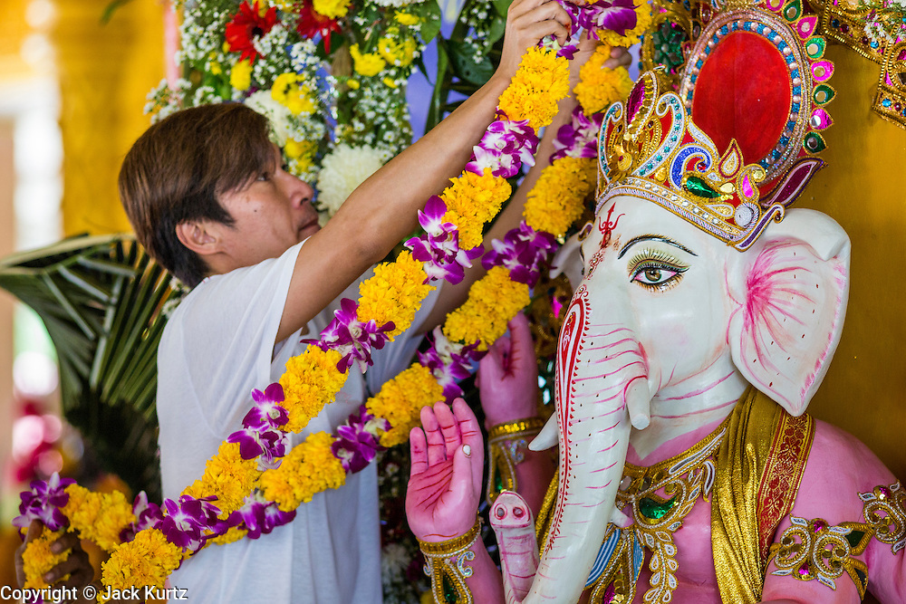 "09 SEPTEMBER 2013 - BANGKOK, THAILAND:  A Thai Hindu places a flower garland on a statue of Ganesha at the Shiva Temple in Bangkok. Ganesha Chaturthi also known as Vinayaka Chaturthi, is the Hindu festival celebrated on the day of the re-birth of Lord Ganesha, the son of Shiva and Parvati. The festival, also known as Ganeshotsav (""Festival of Ganesha"") is observed in the Hindu calendar month of Bhaadrapada. The date usually falls between 19 August and 20 September. The festival lasts for 10 days, ending on Anant Chaturdashi. Ganesha is a widely worshipped Hindu deity and is revered by many Thai Buddhists. Ganesha is widely revered as the remover of obstacles, the patron of arts and sciences and the deva of intellect and wisdom.    PHOTO BY JACK KURTZ"