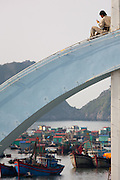 A man with a mobile (cell) phone sitting on Cat Ba harbour ferry terminal arch above fishing boats in Cat Ba Harbour, Vietnam