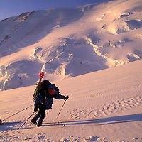 USA, Alaska, Denali National Park, (MR) Climber skis with heavy packs up Kahiltna Glacier on Mt. McKinley