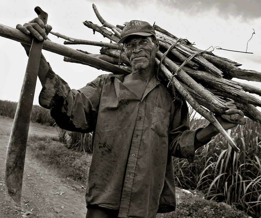 Batey 50, Dominican Republic- A Haitian sugarcane cutter in Batey 50 carries a bundle of cut cane. The workers earn an average of less than $3 per day and are housed in worker communities known as bateyes. These small villages often have deplorable and unsanitary <br /> living conditions.  (Photo by Robert Falcetti)