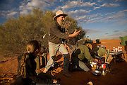 Camel Trek just outside William Creek in North Eastern South Australia.  Philp Gee telling stories at camp after a day of treking. Considered to be one of Australia's leading camel men Philip Gee has been a senior guide with Explore the Outback camel safaris since 1987 and he has trained hundreds of wild camels. Philip who is a specialist Historian has led countless expeditions into this wilderness over the past 20 years and knows the Lake Eyre desert country very well. Explore the Outback camel safaris are based in the central Australian deserts near William Creek along the Oodnadatta Track (Lake Eyre, South Australia), and operate from April through to October every year.