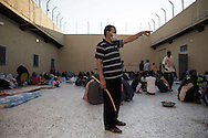 Libya, Garabulli: At Alguaiha detention center, a Libyan guard orders migrants captured at the sea as they were attempting to reach Italy, to go back to their cells as others keep eating in the courtyard of the facility on May 12, 2015. Alessio Romenzi