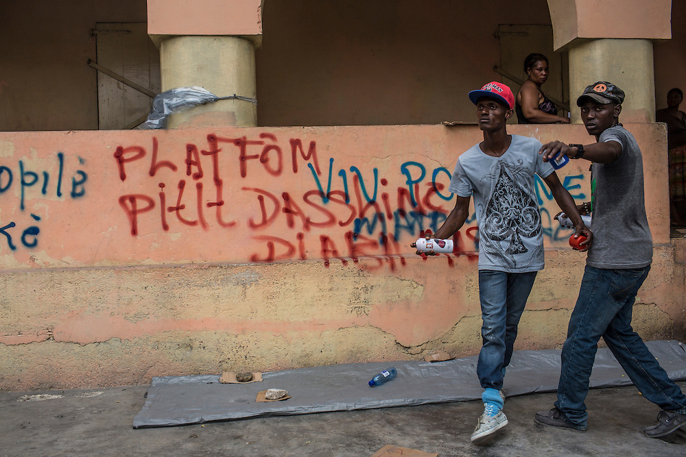 Anti-government protesters after writing anti-Martelly slogans on a wall on Tuesday, December 16, 2014 in Port-au-Prince, Haiti. President Michel Martelly was elected in 2010 with great hope for reforms, but in the wake of slow recovery and parliamentary elections that are three years overdue, his popularity has suffered tremendously, forcing Prime Minister Laurent Lamothe to resign.