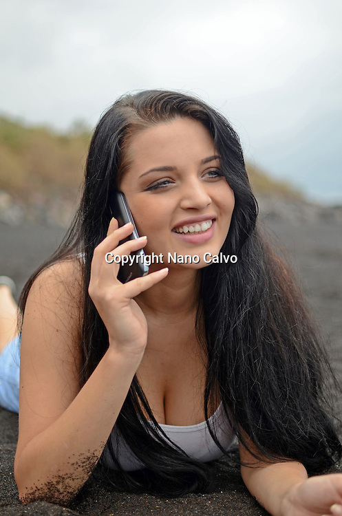 Cute brunette teenager on the beach, talking on the mobile telephone.
