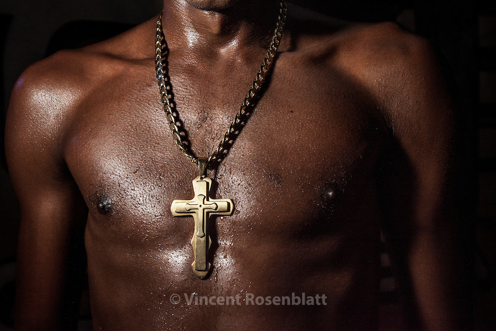 """Crucifix on a """"funkeiro's"""" torso, Baile at Sítio da Boa, in São Gonçalo, Rio de Janeiro far suburb, but with a strong Funk tradition in this poor town ..The Funk carioca movement is fashion and look as well : The boys show off their muscles and naked torsos, adorned with chains and tattoos, accessories which will make the difference during the ball. Girls will look after their bikini marks, which will appear above mini-skirts or micro-shorts. Everything is worth to draw attention!"""