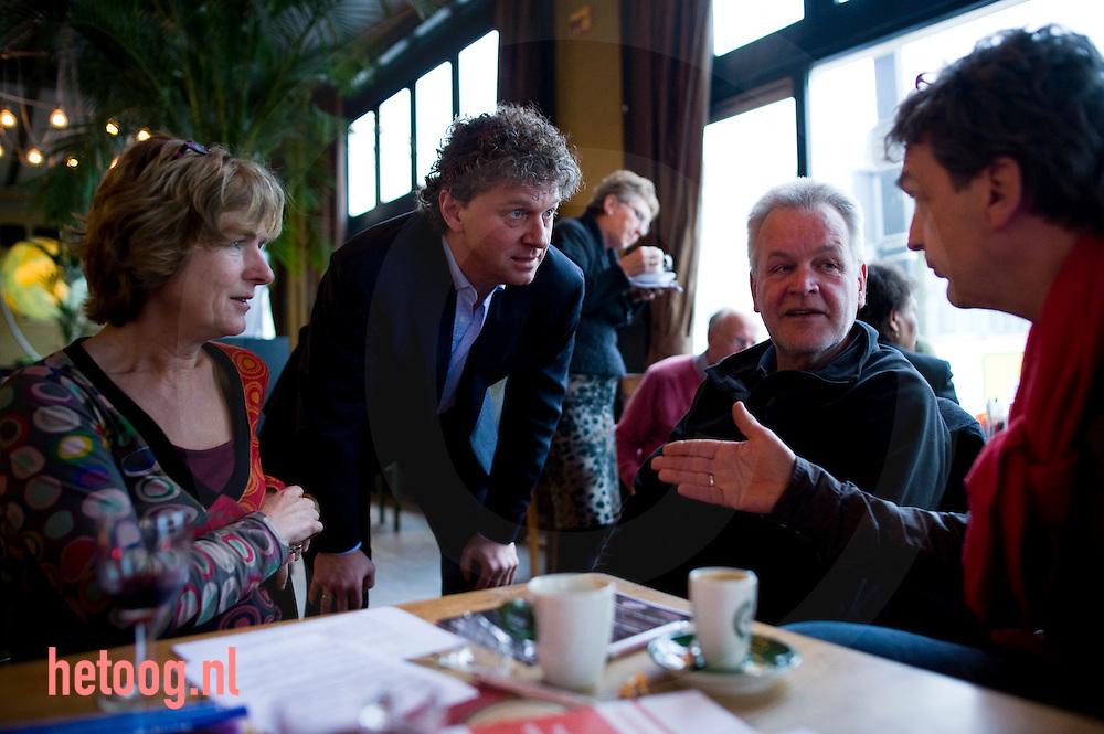 """Jack Monasch (staand) in gesprek met Dick Buursink (tweede van rechts) gedeputeerde in de staten van overijssel in de pauze van het  PvdA lijsttrekkersdebat voor het europeesparlement in """"Media Art Cafe Berlijn"""" in Enschede d.d. 30-11-2008..Aanwezig de vier kandidaten voor de functie van lijsttrekker: Hanna Belliot,Thijs Berman, Kris Douma en Jack Monasch..Verder aanwezig een aantal pvda-ers uit de lokale politiek en bar weinig geinteresserde burgers."""