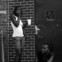 Two highschool age girls hang out in front of an abandoned building in south east Washington.