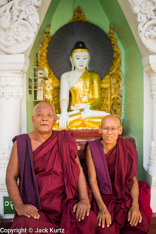 07 JUNE 2014 - YANGON, YANGON REGION, MYANMAR: Buddhist monks in front of a statue of the Buddha at Shwedagon Pagoda in Yangon. Shwedagon Pagoda is officially called Shwedagon Zedi Daw and is also known as the Great Dagon Pagoda and the Golden Pagoda. It's a 99 metres (325ft) gilded pagoda and stupa located in Yangon. It is the most sacred Buddhist pagoda in Myanmar with relics of the past four Buddhas enshrined within: the staff of Kakusandha, the water filter of Koṇāgamana, a piece of the robe of Kassapa and eight strands of hair from Gautama, the historical Buddha.   PHOTO BY JACK KURTZ