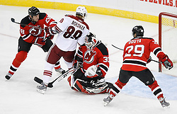 Mar 12, 2009; Newark, NJ, USA; New Jersey Devils goalie Martin Brodeur (30) makes a save while New Jersey Devils defenseman Johnny Oduya (29) and New Jersey Devils defenseman Niclas Havelid (28) defend against Phoenix Coyotes right wing Mikkel Boedker (89) during the third period at the Prudential Center. The Devils defeated the Coyotes 5-2, and Brodeur moved to within one win of tying Patrick Roy for the all-time win record.