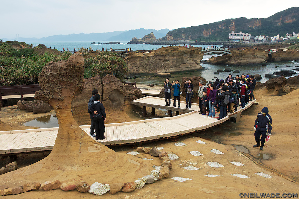"Tourists line up to have their picture taken in front of ""Queen's Head Rock"", probably one of Taiwan's most famous sites."