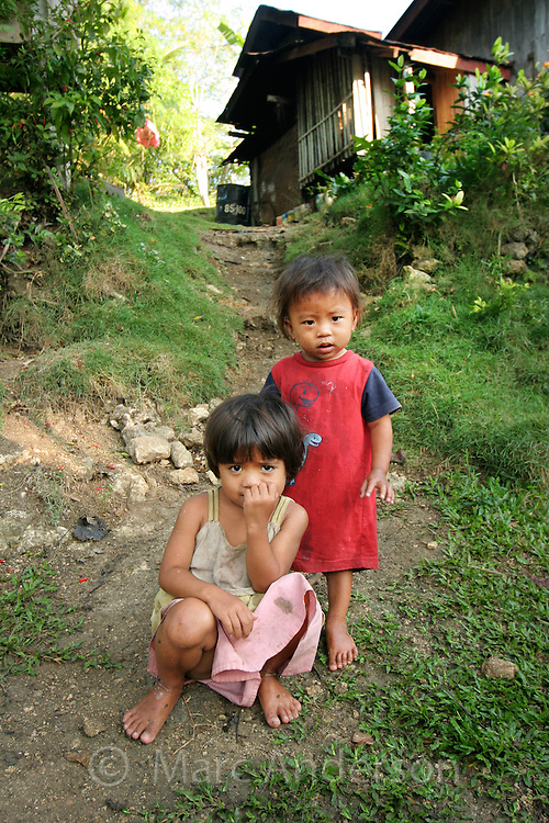 Two little poor girls in front of a small house, Bohol, Philippines..