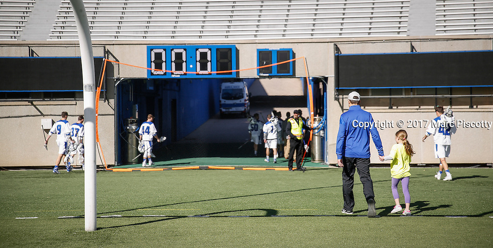 SHOT 2/18/17 2:45:57 PM - Air Force head lacrosse coach Eric Seremet walks off the field with his daughter after losing to Marist College at Falcon Stadium at the Air Force Academy in Colorado Springs, Co. Marist won the game 10-4. Seremet is in his ninth season as the head coach for the Air Force lacrosse program.<br /> (Photo by Marc Piscotty / &copy; 2017)