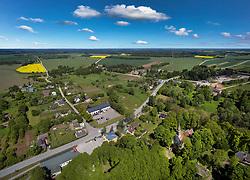 Puhja village, settlement. Agricultural aerial view, landscape, roadside buildings in Estonia.