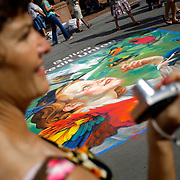 SHOT 6/24/2007 - A passerby is entertained by one of the creations at the 5th annual Comcast La PIazza dell'Arte in Larimer Square in downtown Denver on Sunday June 24, 2007. The streets of the downtown historic district are transformed into a giant canvas as student, amateur and professional artists create temporary works of art on the asphalt. The event follows in the street painting traditions of 16th century Renaissance Italy where madonnari would recreate paintings of the Madonna on the streets with chalk..(Photo by Marc Piscotty/Larimer Square © 2007)