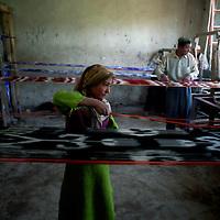 HOTAN: a Uighur girl weaves atlas in a family run factory.