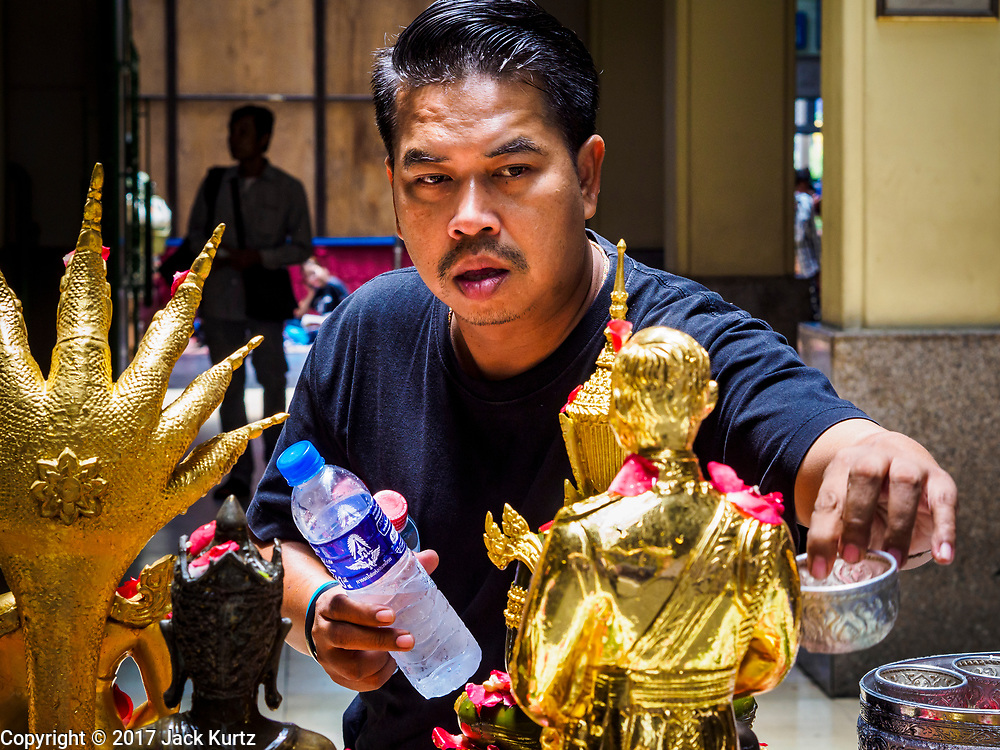 """11 APRIL 2017 - BANGKOK, THAILAND: A man bathes a statue of the Buddha in scented water during the Songkran travel period at Hua Lamphong train station in Bangkok. Songkran is the traditional Thai Lunar New Year. It is celebrated, under different names, in Thailand, Myanmar, Laos, Cambodia and some parts of Vietnam and China. In most places the holiday is marked by water throwing and water fights and it is sometimes called the """"water festival."""" This year's Songkran celebration in Thailand will be more subdued than usual because Thais are still mourning the October 2016 death of their revered Late King, Bhumibol Adulyadej. Songkran is officially a three day holiday, April 13-15, but is frequently celebrated for a full week. Thais start traveling back to their home provinces over the weekend; busses and trains going out of town have been packed.     PHOTO BY JACK KURTZ"""