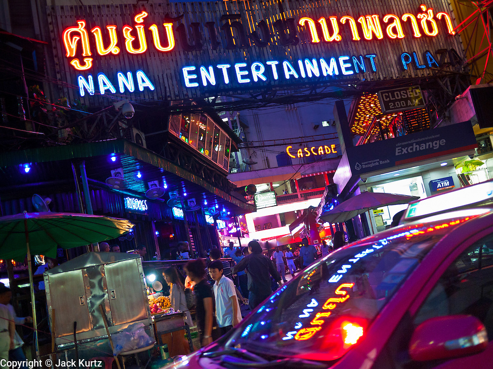 "13 JULY 2011 - BANGKOK, THAILAND:  A taxi passes the entrance to the Nana Entertainment Plaza, a ""red light"" district in Bangkok. Prostitution in Thailand is illegal, although in practice it is tolerated and partly regulated. Prostitution is practiced openly throughout the country. The number of prostitutes is difficult to determine, estimates vary widely. Since the Vietnam War, Thailand has gained international notoriety among travelers from many countries as a sex tourism destination. One estimate published in 2003 placed the trade at US$ 4.3 billion per year or about three percent of the Thai economy. It has been suggested that at least 10% of tourist dollars may be spent on the sex trade. According to a 2001 report by the World Health Organisation: ""There are between 150,000 and 200,000 sex workers (in Thailand).""  PHOTO BY JACK KURTZ"