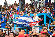 HAVANA, CUBA - MARCH 22, 2016: Fans cheer in the stands and wave a Cuban flag during the game between the Tampa Bay Rays and the Cuban National Team at Estadio Latinoamericano on March 22, 2016 in Havana, Cuba. (Photo by Jean Fruth)