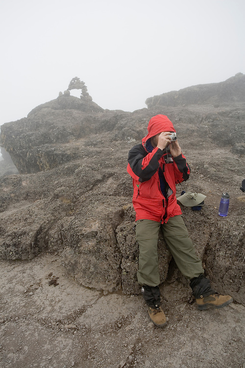 Africa, Tanzania, Kilimanjaro National Park, (MR)Climber takes snapshots in dense fog at top of Barranco Wall near Karanga Camp (13000') on climbing expedition