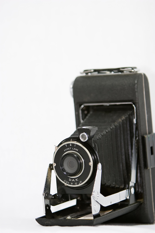 An old style bellows camera on white background.