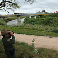 Leonel Guerrero, a Senior Patrol Agent with the U.S. Border Patrol, looks out on the US-Mexico border, near the Gateway Bridge that crosses the Rio Grande, the river marks the border between the U.S. and Mexico in Texas, in Brownsville, TX on April 21, 2010. (Photo/Scott Dalton)