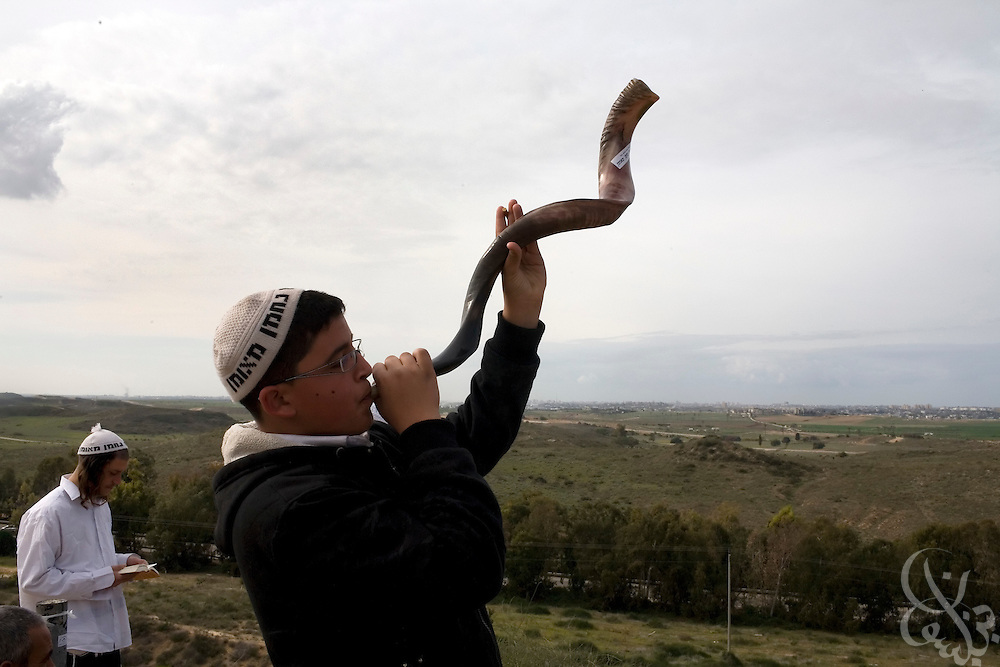 An Israeli member of the Jewish Breslav Hassidim sect plays a Shofar, a horn made out of a rams horn as he and other sect members and townspeople of Sderot watch the ongoing Israeli Defense Forces attack on nearby Gaza (seen behind) January 08, 2009 from a hilltop in Sderot, Israel. At times there is a circus-like atmosphere on the hilltops near Sderot overlooking Gaza as curious onlookers  and war tourists congregate to watch the ongoing military action less than a few kilometers away. ..