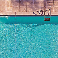 Overhead view of a section of a swimming pool. Bright sunlight on brilliant blue water.