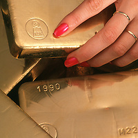 Gold ingots with woman's hand.<br />
