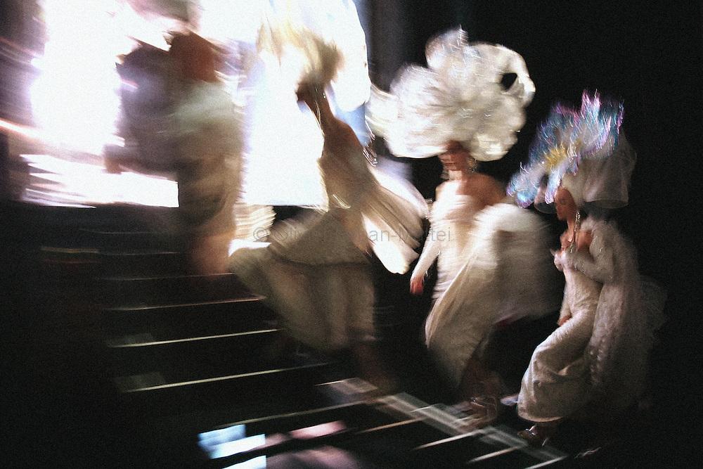 """Des danseuses montent sur scËne le 16 Octobre 2006 au Lido ? Paris. Le """"plus cÈlËbre cabaret du monde"""", qui fÍte ses 60 ans jusquíen juillet 2007, prÈsente tous les soirs la revue """"Bonheur"""", ? laquelle participent 60 """"Bluebells Girls and Boys"""", selectionnÈs sur des critËres stricts : minimum 1,75m pour les danseuses et 1,83 m pour les danseurs. En coulisse le Lido, qui accueille un demi-million de clients et Ècoule 300.000 bouteilles de champagne par an - ce qui en fait le premier Ètablissement mondial consommateur de champagne - emploie prËs de 400 personnes. Une noria de techniciens, machinistes ou couturiers gr,ce ? qui, tous les soirs, la lÈgende du Lido se perpÈtue. ..Dancers get on stage, 16 october 2006 at """"Le Lido"""" in Paris. The famous French cabaret on the Champs-Elysees will celebrate its 60th anniversary until July 2007. 500,000 spectators a year enjoy the glamorous show performed by 60 strictly selected dancers - including 25 topless """"bluebell girls"""" -, whereas, in the wings, 400 stage technicians, mechanics and craftsmen help to make the legend comes true.   AFP PHOTO OLIVIER LABAN-MATTEI"""