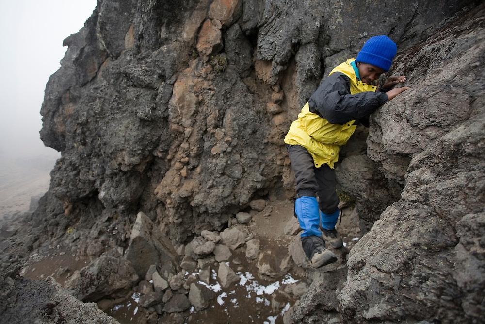 Africa, Tanzania, Kilimanjaro National Park, (MR) Climbing guide rock climbs toward top of Lava Tower above camp (15100') on Mount Kilimanjaro climbing expedition