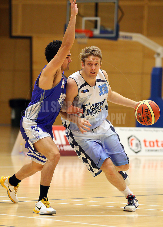 PERTH, AUSTRALIA - JULY 16: Adam Nener of the Tigers looks to drive past Luke Riches of the Hawks during the week 18 SBL game between the Perry Lakes Hawks and the Willetton TIgers at The State Basketball Center on July 16, 2011 in Perth, Australia.  (Photo by Paul Kane/Allsports Photography)