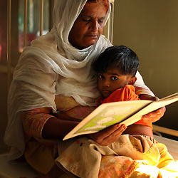 Zarina Bibi reads to her granddaughter Parwesha, 4, who is being treated for stomach pain inside the Children's Hospital at the Pakistan Institute of Medical Sciences, P.I.M.S., in Islamabad, Pakistan on Sept. 18, 2007.