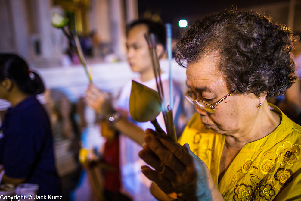 "25 FEBRUARY 2013 - BANGKOK, THAILAND: A woman participates in a procession around Wat Benchamabophit Dusitvanaram (popularly known as either Wat Bencha or the Marble Temple) on Makha Bucha Day. Thais visit temples throughout the Kingdom on Makha Bucha Day to make merit and participate in candle light processions around the temples. Makha Bucha is a Buddhist holiday celebrated in Myanmar (Burma), Thailand, Cambodia and Laos on the full moon day of the third lunar month (February 25 in 2013). The third lunar month is known in Thai is Makha. Bucha is a Thai word meaning ""to venerate"" or ""to honor"". Makha Bucha Day is for the veneration of Buddha and his teachings on the full moon day of the third lunar month. Makha Bucha Day marks the day that 1,250 Arahata spontaneously came to see the Buddha. The Buddha in turn laid down the principles his teachings. In Thailand, this teaching has been dubbed the 'Heart of Buddhism'.      PHOTO BY JACK KURTZ"
