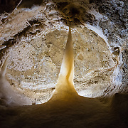 """A sharp tooth shape appears in a rocky mouth of Caverns of Sonora, Sutton County, Texas, USA. The world-class Caverns of Sonora have a stunning and sparkling array of speleothems (helictites, stalactites, stalagmites, flowstone, coral trees, and other calcite crystal formations). National Speleological Society co-founder, Bill Stephenson said, after seeing it for the first time, """"The beauty of Caverns of Sonora cannot be exaggerated...not even by a Texan!"""" Geologically, the cave formed between 1.5 to 5 million years ago within 100-million-year-old (Cretaceous) Segovia limestone, of the Edward limestone group. A fault allowed gases to rise up to mix with aquifer water, making acid which dissolved the limestone, leaving the cave. Between 1 and 3 million years ago, the water drained from the cave, after which speleothems begain forming. It is one of the most active caves in the world, with over 95% of its formations still growing. Sonora Caves are on Interstate 10, about half-way between Big Bend National Park and San Antonio, Texas."""