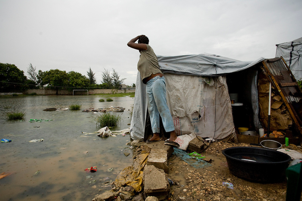 Gislene St. Jean looks out at the water encroaching on her tent. St. Jean's home collapsed during the earthquake and she has been living in the camp since January.