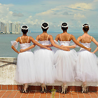 MR. Model relased photo. Four ballerinas in white dresses hold each other from the waist, while looking at Panama´skyline.