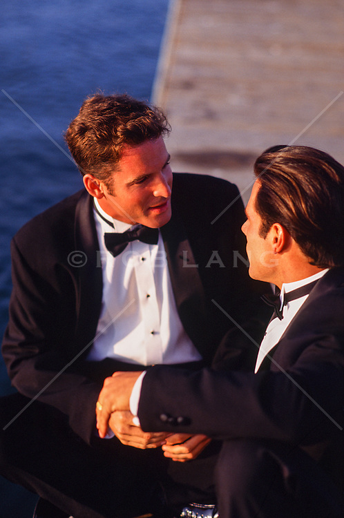 two men in tuxedos holding hands