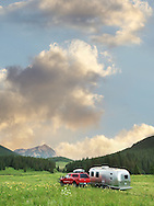 An Airstream trailer and red truck camping in a picturesque meadow near Crested Butte, Colorado.
