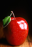 Studio still life of a red apple with a leaf.