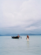 The island officer wading ashore while carrying his wife on Ross & Smith Islands, North Andaman