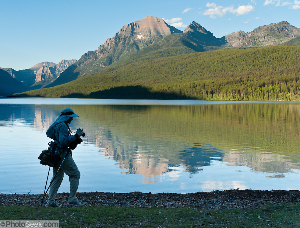 A photographer walks the shore of Bowman Lake, Glacier National Park, Montana, USA